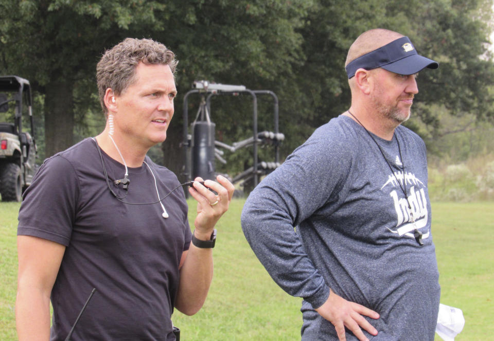 """Director Greg Whiteley and Independence Community College football coach Jason Brown watch a practice during a shoot for the Netflix series """"Last Chance U."""" in Independence, Kan. (Dion Lefler/The Wichita Eagle via AP)"""