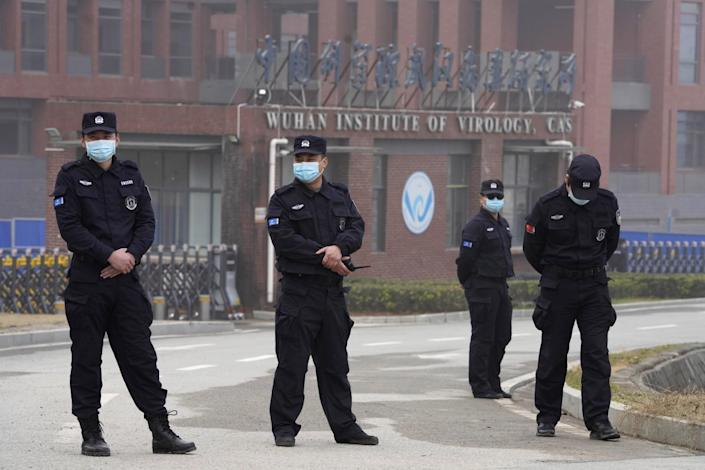 """Four men in uniforms and masks stand on a roadway outside a building with a sign """"Wuhan Institute of Virology."""""""