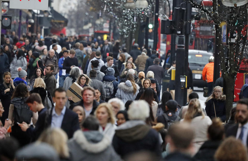 Shoppers walk along Oxford Street in London ahead of Christmas, Friday, Dec. 22, 2017. (AP Photo/Frank Augstein)