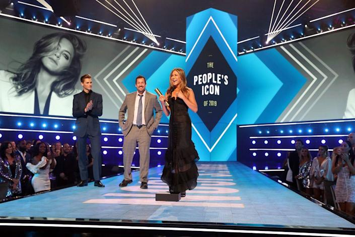 """<p>In 2019, Aniston was honored as the <a href=""""https://www.elle.com/uk/life-and-culture/a29754229/jennifer-aniston-peoples-choice-awards-speech/"""" rel=""""nofollow noopener"""" target=""""_blank"""" data-ylk=""""slk:People's Icon"""" class=""""link rapid-noclick-resp"""">People's Icon</a> at the E! People's Choice Awards. She was presented the award by her Murder Mystery co-star, Adam Sandler. An emotional Aniston thanked the crowd and her fans at home for """"being on this journey with me"""" and """"sticking by me.""""</p>"""