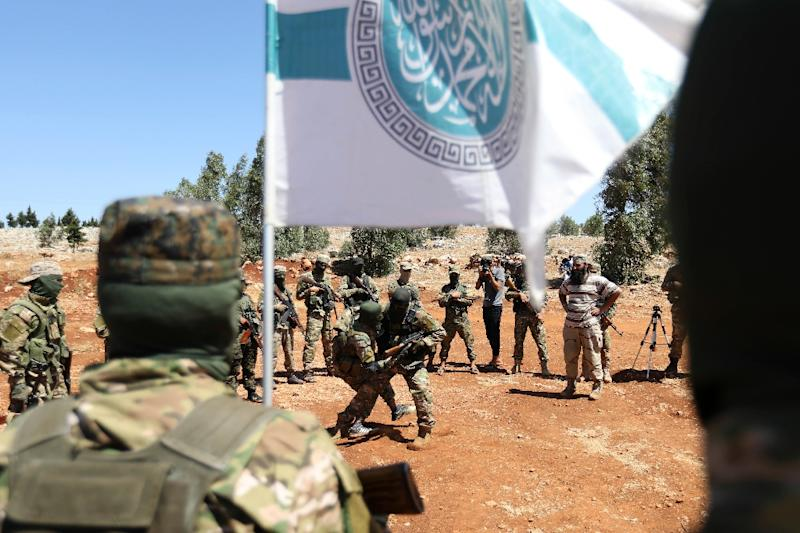 Rebel fighters take part in a mock battle as they prepare for an expected Syrian government offensive on Idlib province at a training camp of Hayat Tahrir al-Sham on August 14, 2018 (AFP Photo/OMAR HAJ KADOUR)