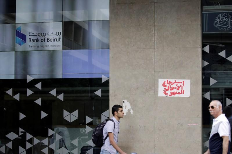 Two men walk past a closed bank office in Beirut