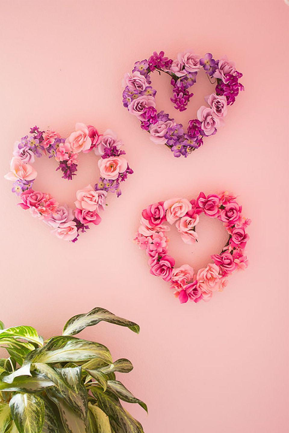 """<p>Use bunches of artificial flowers to make elegant wreaths for your walls or front door. </p><p><strong>Get the tutorial at <a href=""""http://www.designimprovised.com/2015/01/diy-floral-hearts.html?m=1"""" rel=""""nofollow noopener"""" target=""""_blank"""" data-ylk=""""slk:Design Improvised"""" class=""""link rapid-noclick-resp"""">Design Improvised</a>.</strong> </p><p><strong><span class=""""redactor-invisible-space""""><a class=""""link rapid-noclick-resp"""" href=""""https://www.amazon.com/s/ref=nb_sb_noss_2?url=search-alias%3Darts-crafts&field-keywords=heart+wreath+form&tag=syn-yahoo-20&ascsubtag=%5Bartid%7C10050.g.2971%5Bsrc%7Cyahoo-us"""" rel=""""nofollow noopener"""" target=""""_blank"""" data-ylk=""""slk:SHOP HEART WREATH FORMS"""">SHOP HEART WREATH FORMS</a><br></span></strong></p>"""