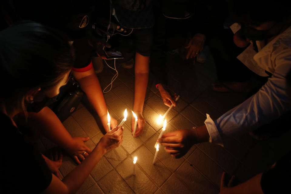 Pro-democracy supporters light candle during a protest in Bangkok, Thailand, Tuesday, Aug. 3, 2021. A Thai protest leader on Tuesday renewed calls for the reform of the country's monarchy and suggested that time was running out for the powerful institution to respond. (AP Photo/Anuthep Cheysakron)
