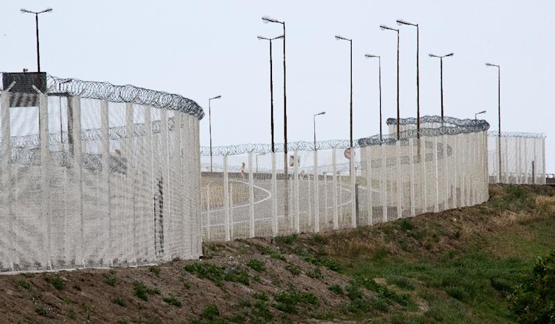 A metal fence erected to prevent migrants trying to cross the Channel to reach Britain from climbing into the back of UK-bound trucks is pictured in the northern French port of Calais on July 7, 2015 (AFP Photo/Denis Charlet)