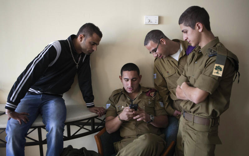 "In this photograph made on Sunday, Dec. 22, 2013, Israeli soldiers stand before the ""Israeli Christians Recruitment Forum"" in Nazareth. Army service in Israel is mandatory for Jews, though not all are called up. Druze leaders signed up their community for army service in the 1950s, and Druze men have been conscripted ever since, while Muslims and Christians are not required to serve. (AP Photo/Dan Balilty)"