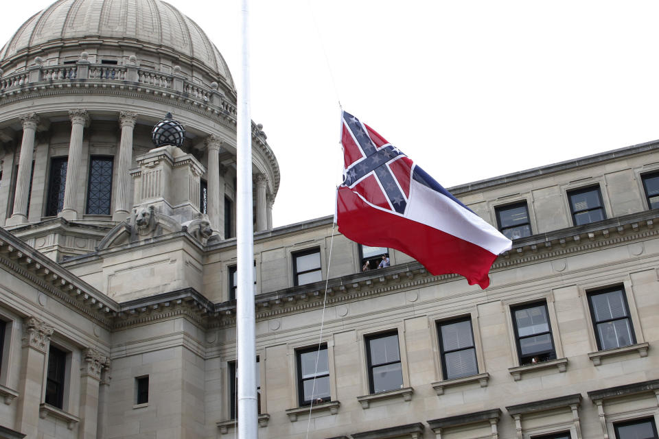 The retired Mississippi state flag is raised over the Capitol grounds one final time in Jackson, Miss., Wednesday, July 1, 2020. The banner was the last state flag with the Confederate battle emblem on it. (AP Photo/Rogelio V. Solis)
