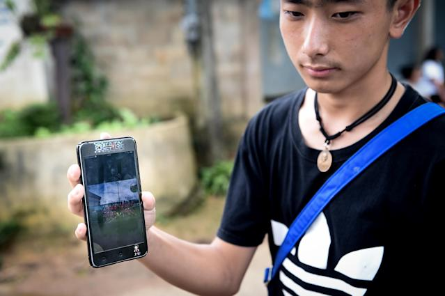 <p>Thananchai Saengtan, 15, shows a photo of his missing friends at soccer pitch near Tham Luang CavePin Chiang Rai province on July 1, 2018 as the rescue operation continues for the missing children and their coach. (Photo: Lillian Suwanrumpha/AFP/Getty Images) </p>