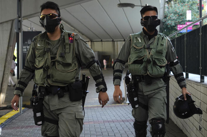 Riot police wearing masks patrol outside of a polling place in Hong Kong, Sunday, Nov. 24, 2019. Long lines formed outside Hong Kong polling stations Sunday in elections that have become a barometer of public support for anti-government protests now in their sixth month. (AP Photo/Vincent Yu)