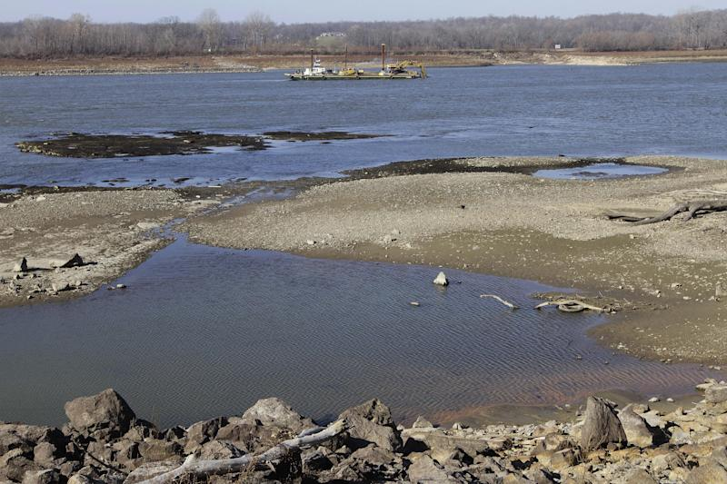 Barges with excavating machinery are seen working on the Mississippi River Tuesday, Dec. 18, 2012, in Thebes Ill. The Army Corps of Engineers is delaying the use of explosives to blast away treacherous rock pinnacles on the Mississippi River because crews are having so much success removing the rocks with excavating machinery. (AP Photo/Seth Perlman)