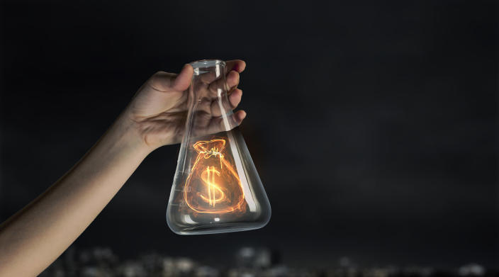 Glowing money bag in a flask.
