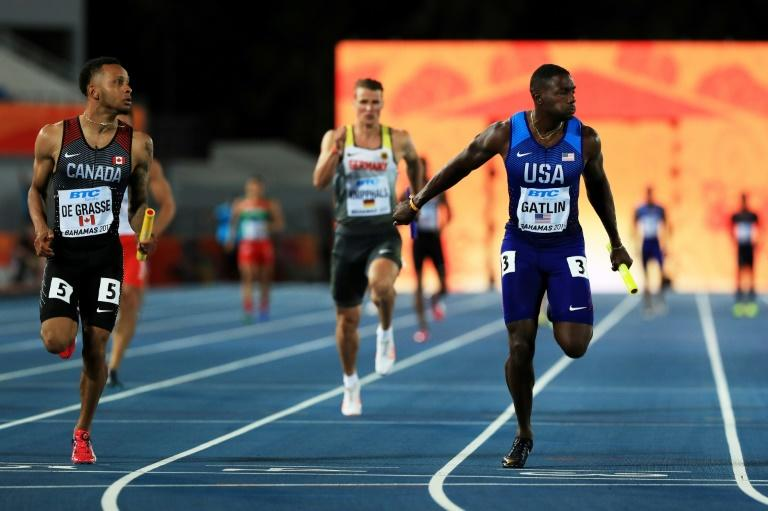 Andre De Grasse (L) of Canada and Justin Gatlin of the US cross the finish line during the IAAF/BTC World Relays Bahamas 2017, at Thomas Robinson Stadium in Nassau, on April 22