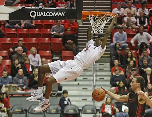 San Diego State forward Dwayne Polee hangs from the rim after slamming in a basket against Saint Katherine during the first half of an NCAA college basketball game on Friday, Dec. 27, 2013,3 in San Diego. (AP Photo/Lenny Ignelzi)