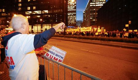 A supporter of Republican president-elect Donald Trump signals to protesters outside Trump International Hotel and Tower in Chicago