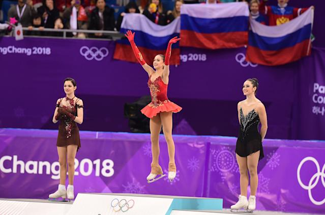 <p>Bronze medallist Canada's Kaetlyn Osmond (R), and silver medallist Russia's Evgenia Medvedeva (L) look on as gold medallist Russia's Alina Zagitova celebrates on the podium during the venue ceremony after the women's single skating free skating of the figure skating event during the Pyeongchang 2018 Winter Olympic Games at the Gangneung Ice Arena in Gangneung on February 23, 2018. / AFP PHOTO / Roberto SCHMIDT </p>