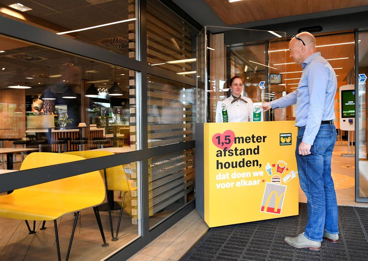 A man takes a number at a prototype location of fast food giant McDonald's for restaurants which respect the 1.5m social distancing measure, amid the coronavirus disease (COVID-19) outbreak, in Arnhem, Netherlands, May 1, 2020. REUTERS/Piroschka van de Wouw