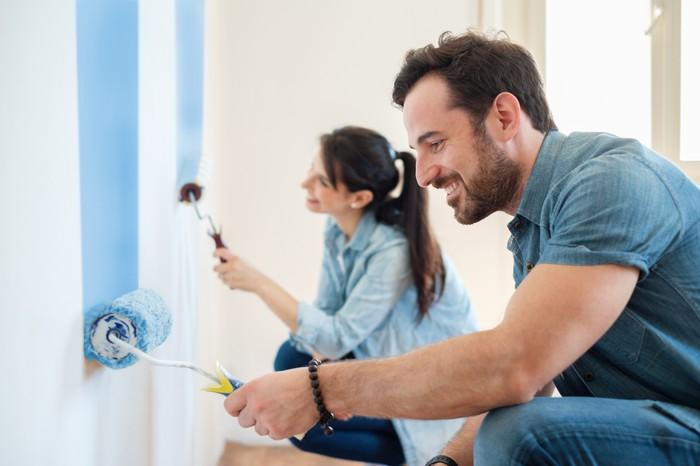 A man and woman paint the wall with rollers in a room.