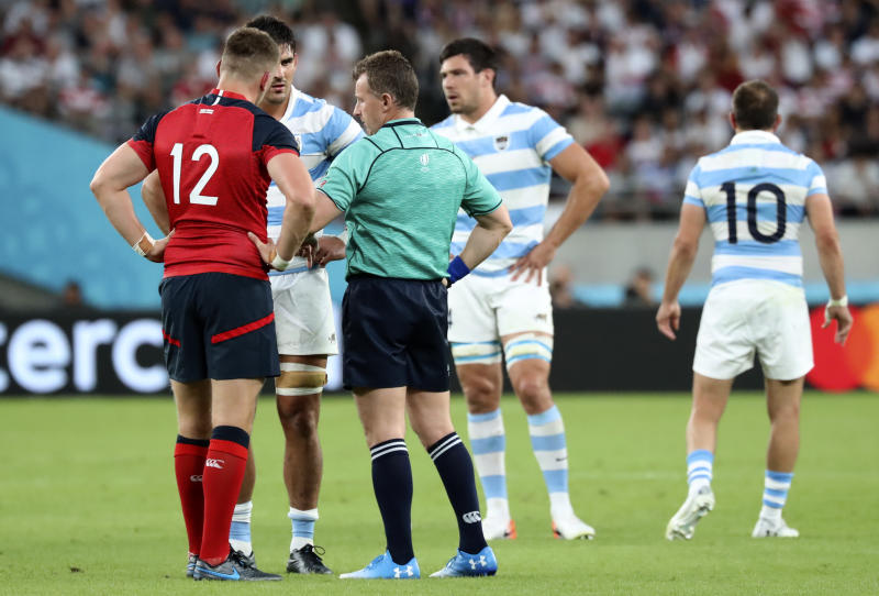 Referee Nigel Owens talks to team captain's England's Owen Farrell, left, and Argentina's Pablo Matera following a player scuffle during the Rugby World Cup Pool C game at Tokyo Stadium between England and Argentina in Tokyo, Japan, Saturday, Oct. 5, 2019. (AP Photo/Eugene Hoshiko)