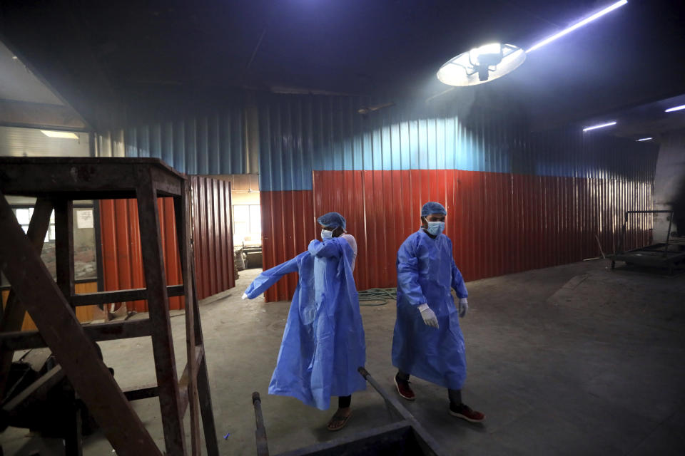 Workers put on personal protective suits before carrying the body of a COVID-19 victim for cremation in New Delhi, India, Wednesday, Sept. 16, 2020. India is now second in the world with the number of reported coronavirus infections with over 5.1 million cases, behind only the United States. Its death toll of only 83,000 in a country of 1.3 billion people, however, is raising questions about the way it counts fatalities from COVID-19. (AP Photo/Manish Swarup)