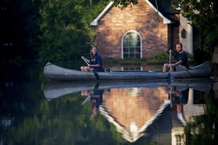 Danny and Alys Messenger canoe away from their flooded home after reviewing the damage in Prairieville, La., Tuesday, Aug. 16, 2016. (Photo: Max Becherer/AP)
