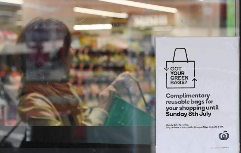 A sign notifying customers of reusable plastic bags is seen at a Woolworths Sydney CBD store.