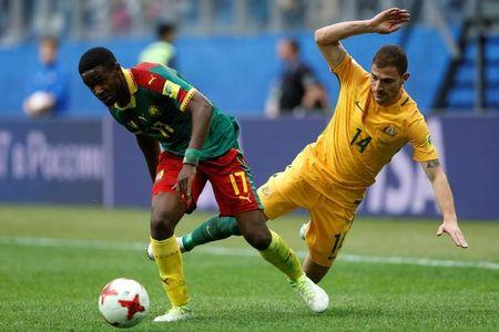 Cameroon's Arnaud Djoum in action with Australia's James Troisi.    REUTERS/Carl Recine
