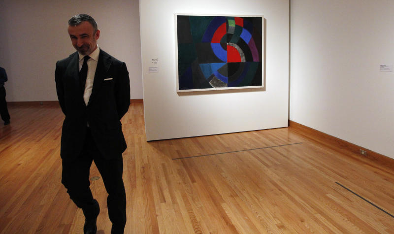 In this photo taken Tuesday, Oct. 9, 2012, Alain Seban, president of the museum at the Pompidor Center, walks past an oil painting by Oil by Sonia Delaunay (Profound Rhythm, 1960), as part of one of two new exhibits featuring art exclusively by women at the Seattle Art Museum, in Seattle. Included in the exhibition is the only U.S. stop for an exhibit from the Pompidou Center in Paris, home of the modern art museum there, of painting, sculpture, drawing, photography and video. The exhibit runs through Jan. 13, 2013. (AP Photo/Elaine Thompson)