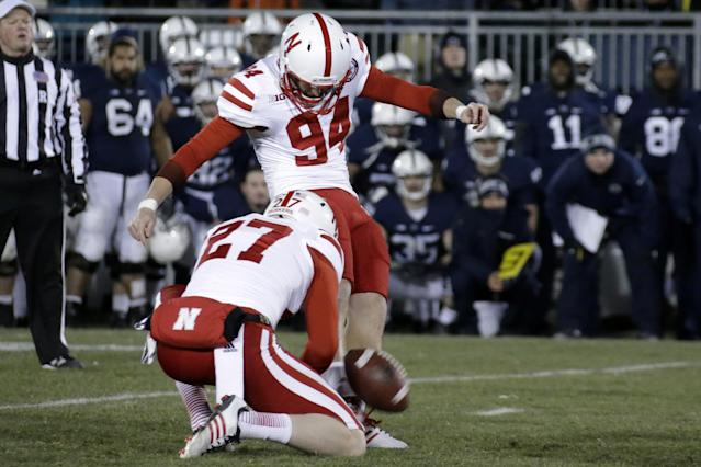 Nebraska kicker Pat Smith (94) kicks the game-winning field goal out of the hold by Nebraska punter Sam Foltz (27) to beat Penn State 23-20 in overtime during an NCAA college football game in State College, Pa., Saturday, Nov. 23, 2013. (AP Photo/Gene J. Puskar)