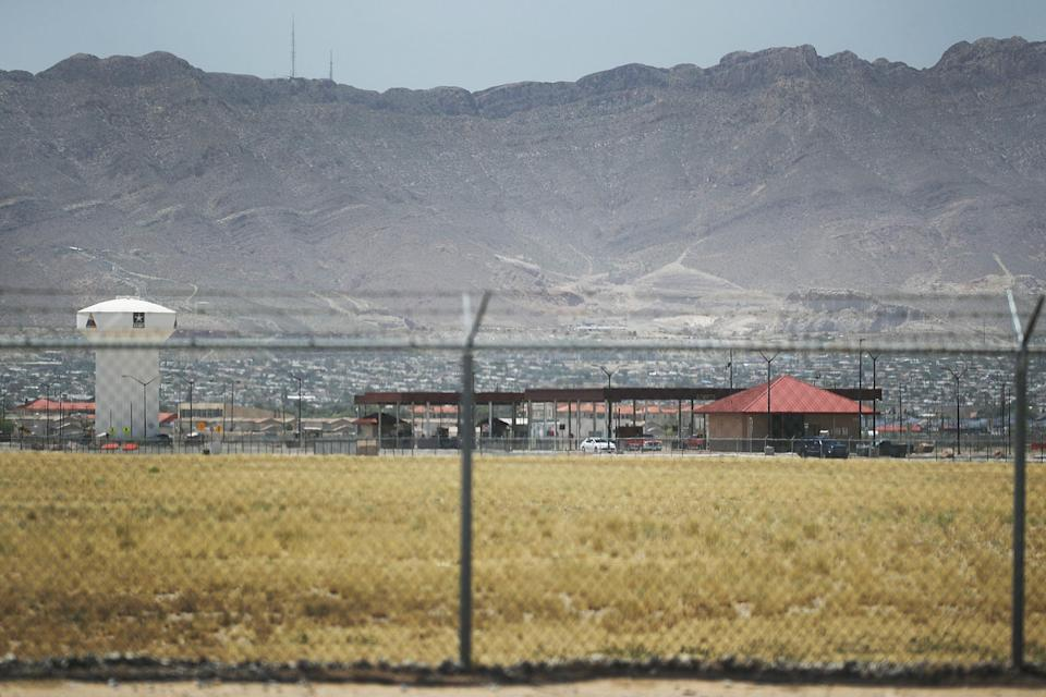 Fort Bliss, which holds temporary housing for migrants, is seen through a fence. (Joe Raedle / Getty Images file)