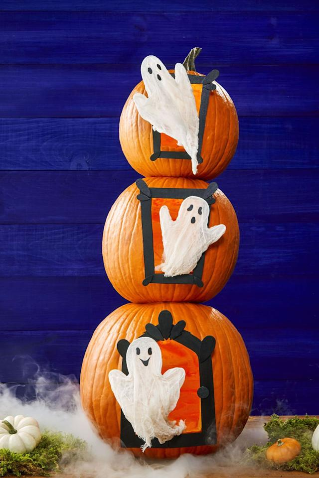 "<p>Choose three orange pumpkins that stack nicely; hollow each from bottom. Draw and cut out your own templates for a door and windows, trace onto pumpkins, and carve. </p><p>Trace each again onto balsa wood sheets; cut out. Paint wood shapes black and hot-glue to frame. Bend 12-gauge aluminum wire into ghost shape, leaving 8-inch excess on both ends. </p><p>Drape cheesecloth over wire; trim excess. Spray with liquid spray starch; allow to dry. Glue black paper faces onto ghosts. Poke ends of wire into interior of pumpkin to secure. <em></em></p><p><strong>What you'll need</strong>: <a href=""https://www.amazon.com/Grafix-Chipboard-12-Inch-Natural-25-Pack/dp/B0013JRFUA/"" target=""_blank"">Balsa Wood Sheets</a> ($13, amazon.com)</p>"