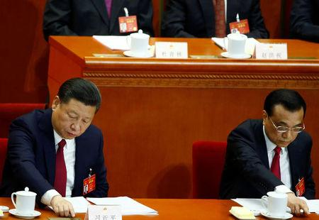 China's President Xi Jinping and China's Premier Li Keqiang press voting buttons during the closing session of China's National People's Congress (NPC) at the Great Hall of the People in Beijing