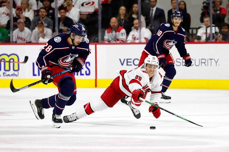 Carolina Hurricanes' Teuvo Teravainen (86) dives at the puck controlled by Columbus Blue Jackets' Oliver Bjorkstrand (28) during the third period of an NHL hockey game, in Raleigh, N.C., Saturday, Oct. 12, 2019.