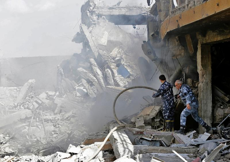 Syrian soldiers inspect the wreckage of a building described as part of the Scientific Studies and Research Centre (SSRC) compound in the Barzeh district, north of Damascus, on April 14, 2018 (AFP Photo/LOUAI BESHARA)