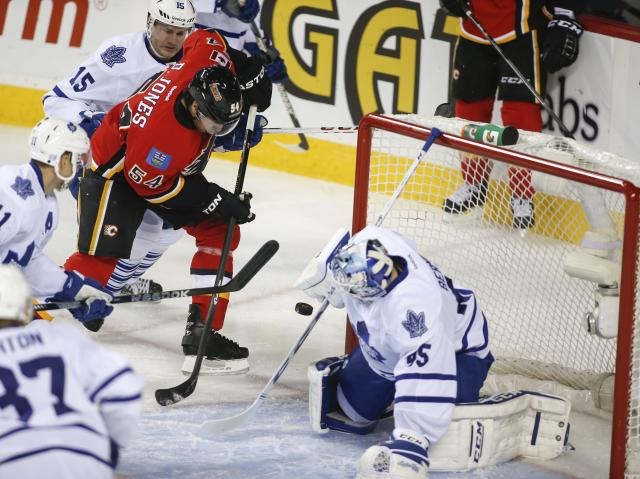 Toronto Maple Leafs goalie Jonathan Bernier, right, stops a shot from Calgary Flames' David Jones during the first period of an NHL hockey game in Calgary, Alberta, Wednesday, Oct. 30, 2013. (AP Photo/The Canadian Press, Jeff McIntosh)