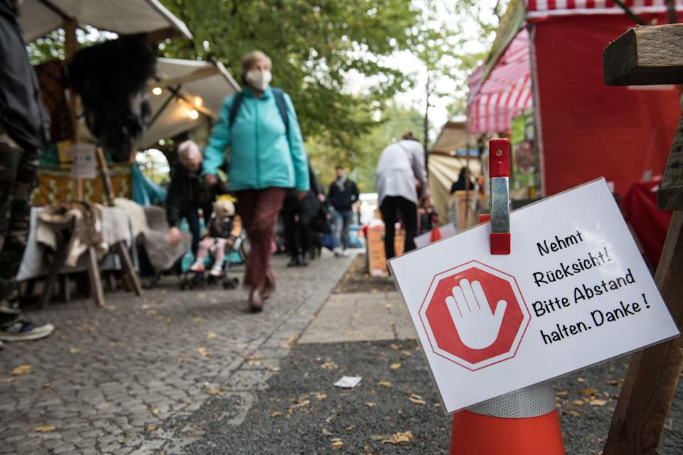 "A sign reading ""Please keep your distance. Thank you."" is seen at the weekly market in Berlin Kreuzberg on October 20, 2020 in Berlin. - The Berlin Senate has tightened the corona requirements in view of the rising number of infections. The state government decided to make masks compulsory for markets and ten busy streets in the capital, as the Senate announced after the session. It also made the ""urgent recommendation"" to wear a mask in public places where the minimum distance of 1.5 metres cannot be maintained. (Photo by STEFANIE LOOS / AFP) (Photo by STEFANIE LOOS/AFP via Getty Images)"