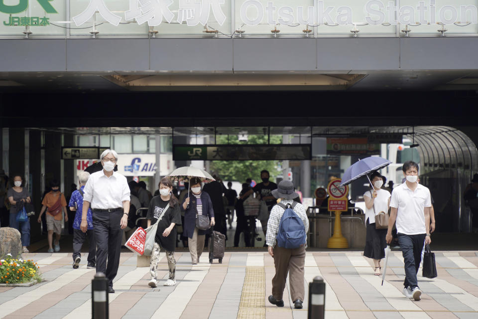 People wearing face masks to help curb the spread of the coronavirus walk around Otsuka Station in Tokyo Friday, July 30, 2021. Japan is set to expand the coronavirus state of emergency in Tokyo to neighboring areas and the western city of Osaka on Friday in the wake of a record-breaking surge in infections while the capital hosts the Olympics. (AP Photo/Kantaro Komiya)