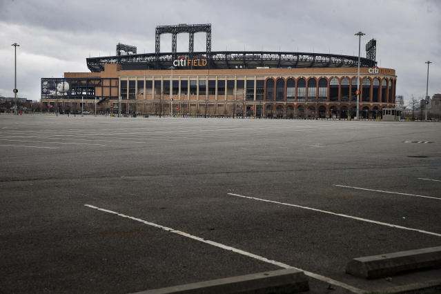 Parking lots sit empty surrounding Citifield, the home of the New York Mets, Wednesday, March 25, 2020, in the Queens borough of New York. There will be empty ballparks on what was supposed to be Major League Baseball's opening day. The start of the regular season is indefinitely on hold because of the coronavirus pandemic. (AP Photo/John Minchillo)