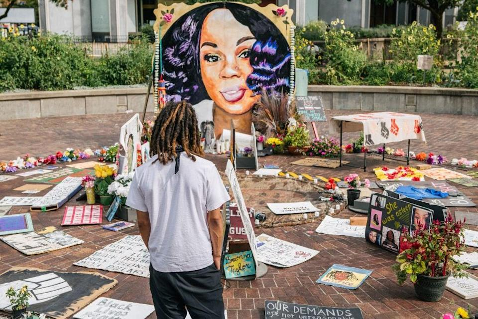 A man looks over a memorial dedicated to Breonna Taylor , who was killed during a police raid on her home (Getty Images)