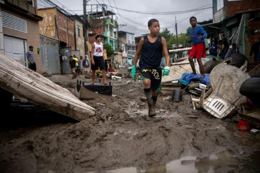 Children walk in the mud following heavy rains during the weekend, in Realengo neighborhood, in the suburbs of Rio de Janeiro, Brazil, on March 2, 2020