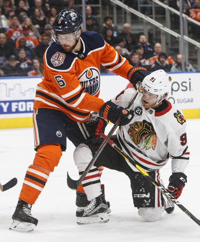 Chicago Blackhawks' Drake Caggiula (91) is checked by Edmonton Oilers' Adam Larsson (6) during the first period of an NHL hockey game Tuesday, Feb. 5, 2019, in Edmonton, Alberta. (Jason Franson/The Canadian Press via AP)