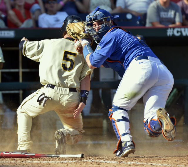 Kent State's T.J. Sutton (5) is tagged out at home plate by Florida catcher Mike Zunino after Alex Miklos reached second base on a fielder's choice in the fifth inning of an NCAA College World Series elimination baseball game in Omaha, Neb., Monday, June 18, 2012. (AP Photo/Ted Kirk)