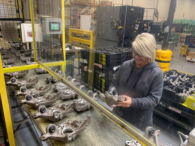 A production worker inspects parts for any quality issues at auto supplier Aludyne in Port Huron
