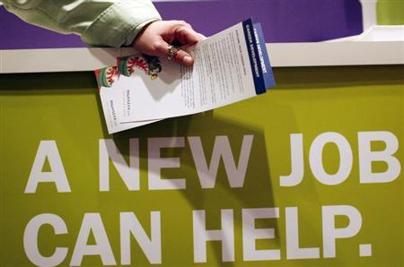 """A man holds pamphlets as he waits at a job fair sponsored by employment website Monster.com as part of their """"Keep America Working"""" tour at a hotel in New York's Times Square, March 5, 2009. REUTERS/Mike Segar"""