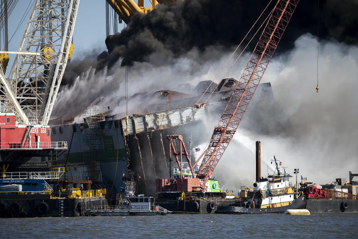 Fire fighters spray water into the cut away mid-section of the cargo vessel Golden Ray, Friday, May 14, 2021, Brunswick, Ga. The Golden Ray had roughly 4,200 vehicles in its cargo decks when it capsized off St. Simons Island on Sept. 8, 2019. Crews have used a giant gantry crane to carve the ship into eight giant chunks, then carry each section away by barge. (AP Photo/Stephen B. Morton)