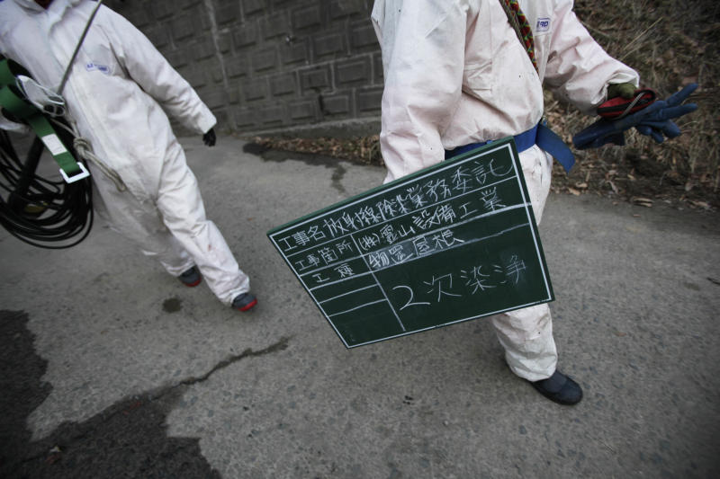 In this photo taken Tuesday, Feb. 21, 2012, workers carry a chalkboard indicating that a warehouse has had its second spray as part of a radiation clean-up program, after they finished work for the day in Fukushima, Japan. A massive cleanup has begun in towns contaminated by radiation leaks from the Fukushima Dai-ichi nuclear plant, but experts leading the government-funded projects say there is no successful example they can follow, and they don't know how to judge the effectiveness of a process that is expected to last for years or even decades. (AP Photo/Greg Baker)