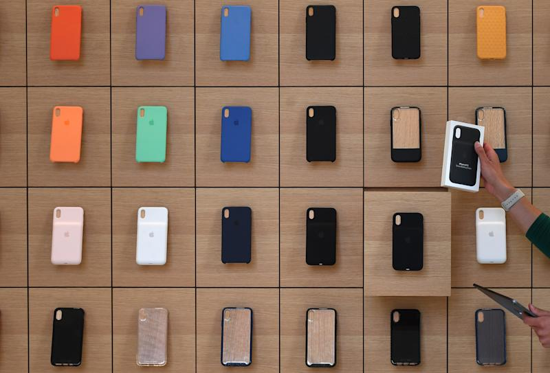 An Apple Store employee takes an iPhone product out of a drawer during the grand opening and media preview of the new Apple Carnegie Library store in Washington, U.S., May 9, 2019. REUTERS/Clodagh Kilcoyne
