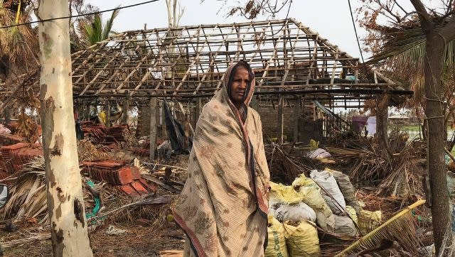 Anwara Baig stands on a pile of rubble that was once her home