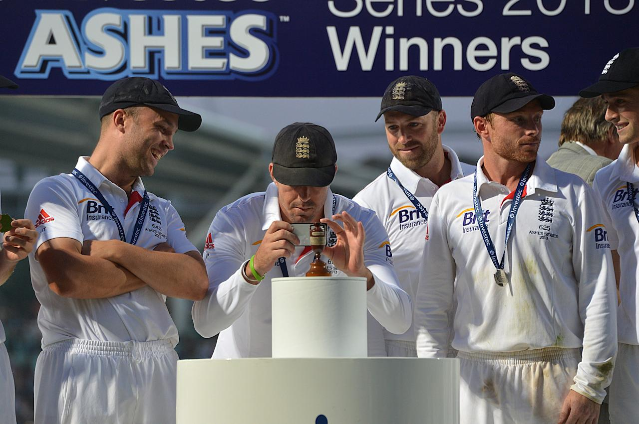 England's Kevin Pietersen takes a photograph of the Ashes Urn