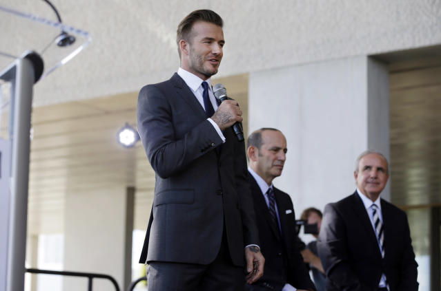 Former England soccer star David Beckham, left, speaks at a news conference where he announced he will exercise his option to purchase a Major League Soccer expansion team in Miami, Wednesday, Feb. 5, 2014. MLS Commissioner Don Garber, center, and Miami-Dade County Mayor Carlos Gimenez listen. (AP Photo/Lynne Sladky)