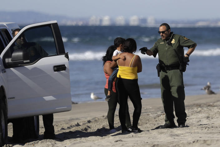 <p>Two Central American women, one carrying a child, are detained by Border Patrol agents after crossing illegally into the United States Wednesday, Nov. 14, 2018, seen from Tijuana, Mexico. (Photo: Gregory Bull/AP) </p>